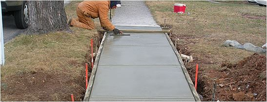 Man Smoothing Out New Concrete Sidewalk